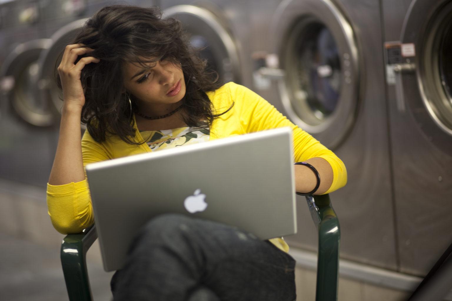 Girl working on laptop at laundrymat